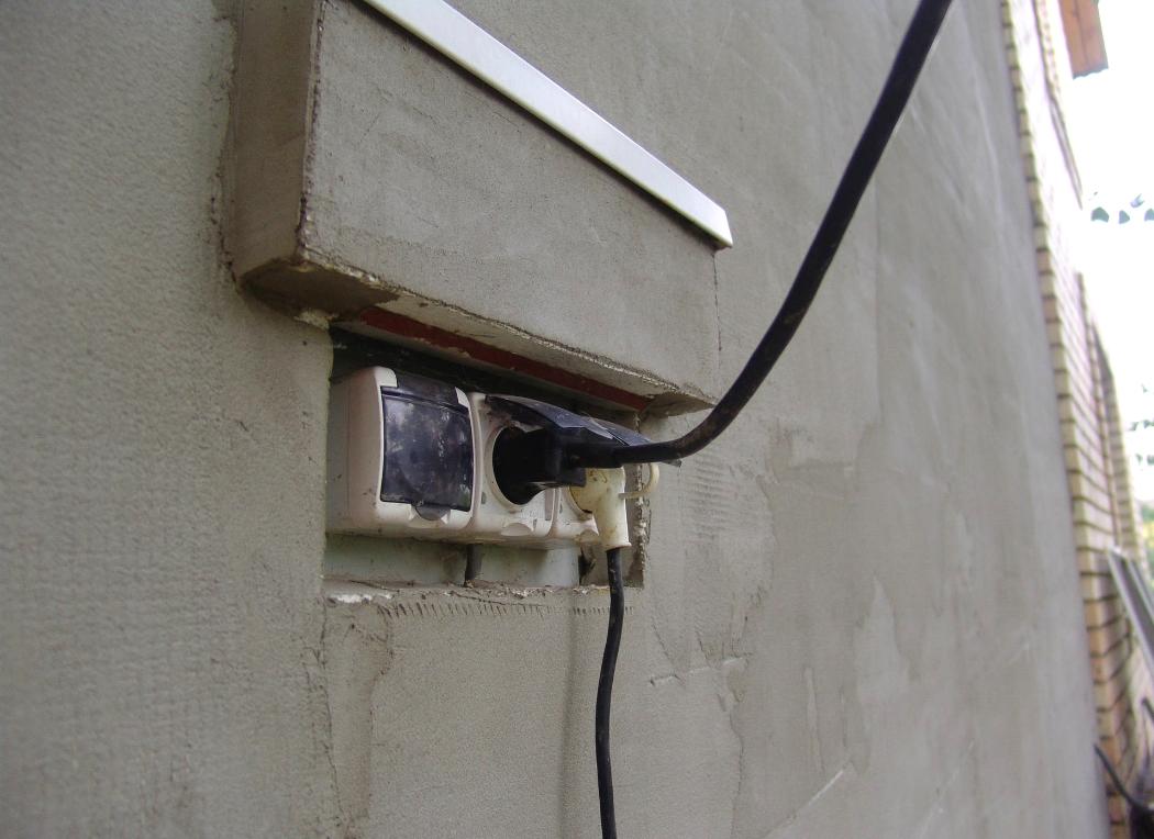 Блок розеток на наружной стене дома
